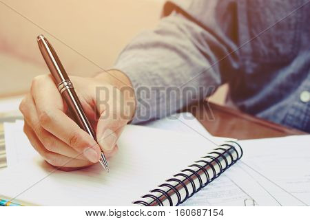 Young asian man writing form filling with register on paper notebook.