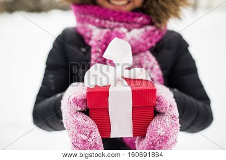 winter holidays, christmas and people concept - close up of happy woman with present or gift box outdoors