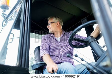 farming, agriculture and people concept - senior man driving tractor at farm
