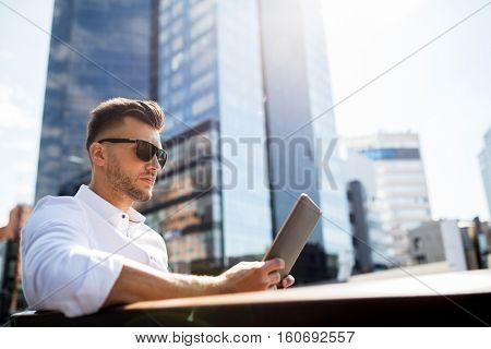 business, education, technology, communication and people concept - man in sunglasses with tablet pc computer sitting on city street bench