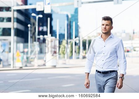 lifestyle and people concept - young man walking along city street