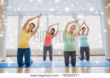 pregnancy, sport, fitness, people and healthy lifestyle concept - group of happy pregnant women exercising on mats in gym over snow