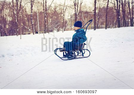 Cute young boy sprayed with snow as he is sledging