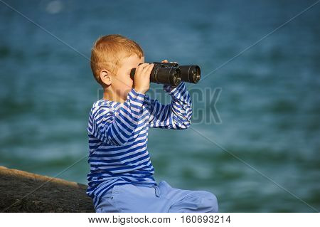 little boy with binoculars , the sea in the background