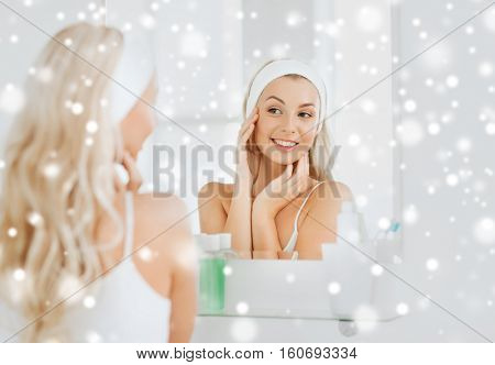 beauty, skin care and people concept - smiling young woman in hairband touching her face and looking to mirror at home bathroom over snow