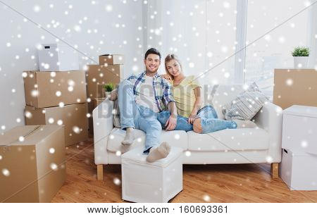 moving, people, repair and real estate concept - happy couple with big cardboard boxes on sofa at new home over snow