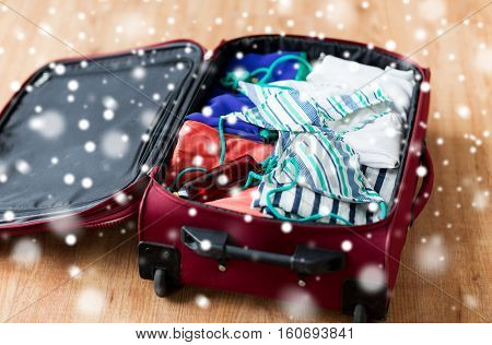 vacation, travel, tourism and objects concept - close up of bag with beach clothes, sunglasses and sunscreen