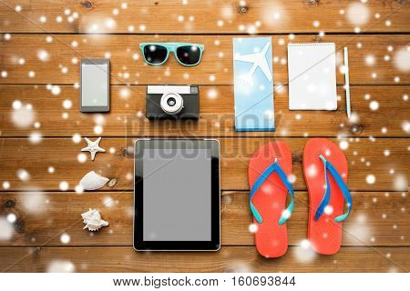 vacation, tourism, winter holidays and objects concept - close up of tablet pc computer and travel stuff