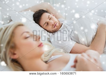 people, rest and relationships concept - happy couple sleeping in bed at home over snow