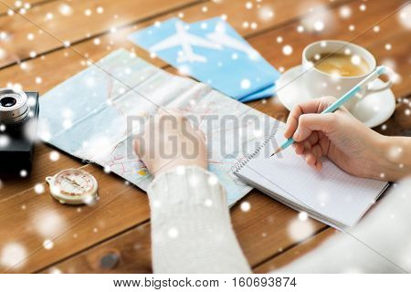 winter holidays, tourism, travel, destination and people concept - traveler hands with map and coffee writing to notebook over snow