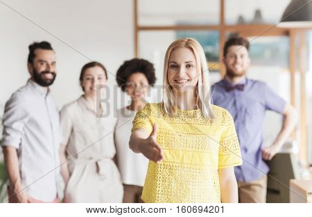 business, startup, people, gesture and teamwork concept - happy young woman greeting by handshake over creative team in office