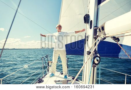 sailing, age, tourism, travel and people concept - happy senior man enjoying freedom on sail boat or yacht floating in sea