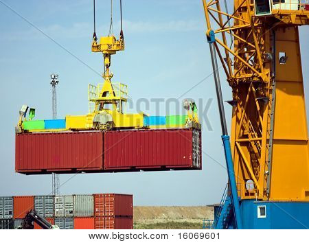 Detail of a large crane carrying containers into a freight ship (logos and brand names carefully removed)