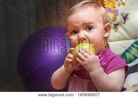 the baby eats a juicy Apple outside his crib