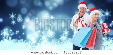 Couple with shopping bags and gifts against snowflake on blue background