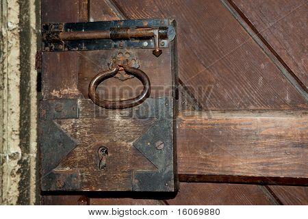 Antique rusty lock on a medieval wooden door