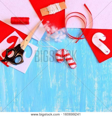 Christmas tree candy cane ornament made of white felt and red ribbon. Candy cane ornament, scissors, thread, felt sheets and scraps, paper template on blue wooden background with blank space for text