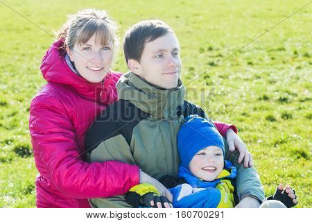 Park family portrait of three people in cold sunny day