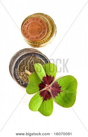 Trébol de cuatro hojas en una pila de monedas de euro