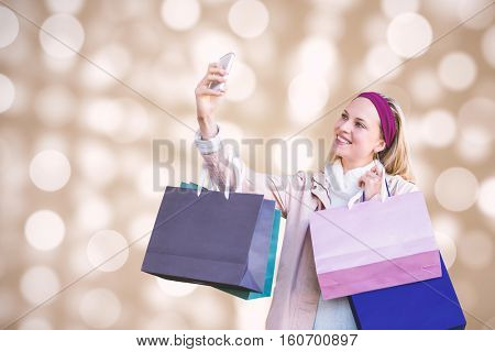 Smiling woman with shopping bags taking selfies against circle design on light background