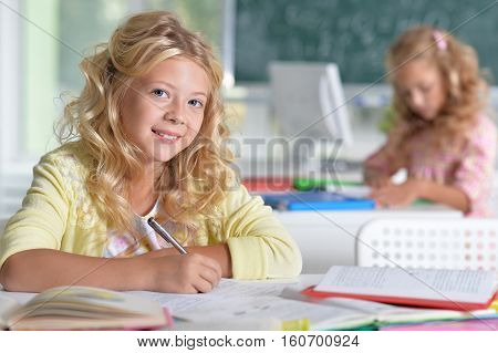 Portrait of a two beautiful little girls at class
