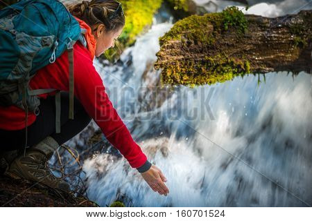 Backpacker Holding Hand Under Running Water Of Clearwater Falls Oregon