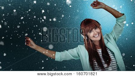 Happy hipster woman listening music with headphone against snow