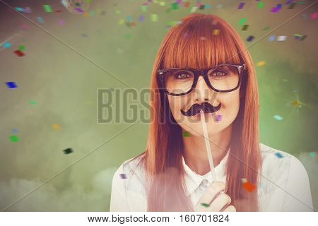 Portrait of a hipster woman with a mustache against smoke at illuminated disco