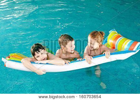 Three little children swimming on pool raft in pool