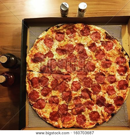 Top view (flat lay) of a large thin crust Pepperoni pizza with accompaniments