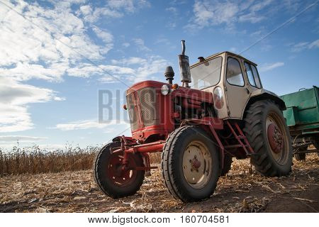 old rusion tractor in field cloudy sky