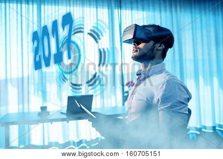 Digital image of new year 2017 against businessman using an oculus