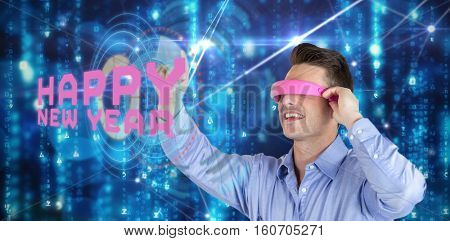 Happy young man gesturing while using virtual reality headset against glowing blue background