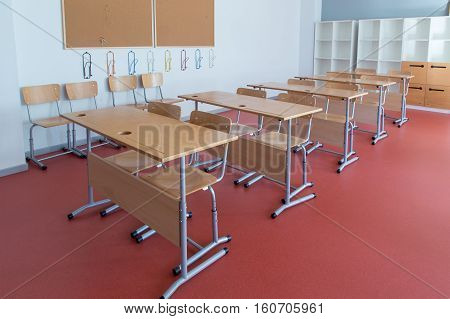 Empty classroom with wooden desks and chairs