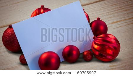 Red christmas baubles surrounding white page against brown wooden background
