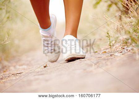 feet of female runner in park nature outdoors