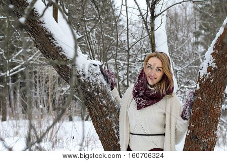 A smiling cheerful girl in in a white sweater and a purple skirt posing with a tree under snow outdoors walks on a winter day in the park.