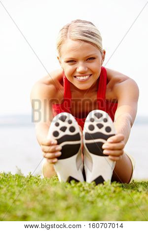 woman doing stretching exercises in nature outdoors
