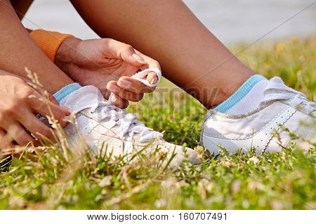 woman sitting on grass tieing shoe-laces in nature outdoors