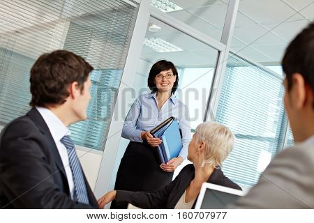 Woman leader greeting her colleagues in office
