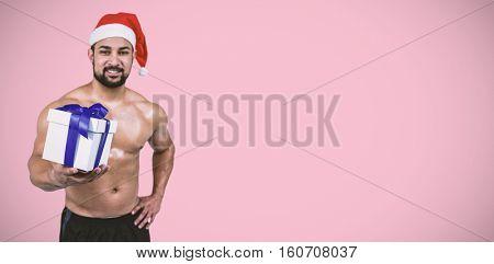 Muscular man in santa hat against pink background
