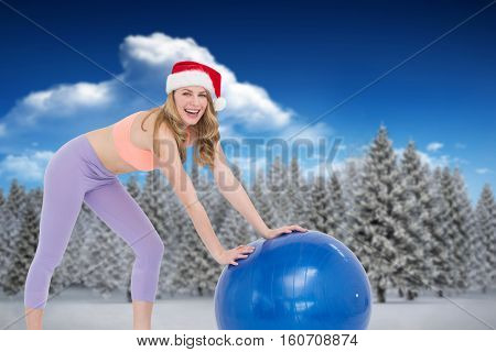 Festive blonde woman using exercise ball against fir tree forest in snowy landscape