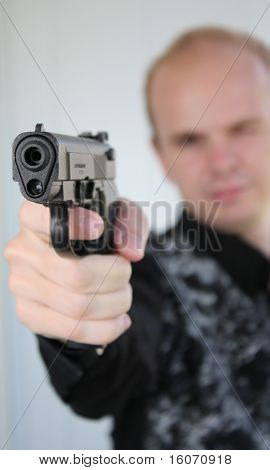 Young man aiming with pistol in hand