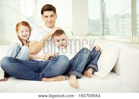 Portrait of a young father with two kids sitting on sofa