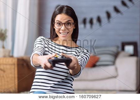 Entertaining myself. Amused cheerful young woman sitting at home and holding the game console while expressing joy and using the modern device