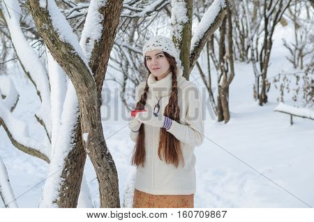 Long-haired brunette girl walking in a winter park and drinking coffee with marshmallow wearing white sweater and a handmade white hat