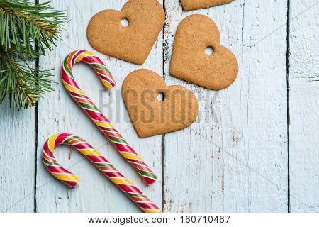 Christmas backgrounds. Christmas decor on wooden background with cookies and cane. View from above