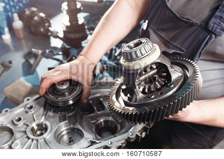 Cross-section of a car gearbox. mechanics work in the garage. hand car mechanic in working clothes.
