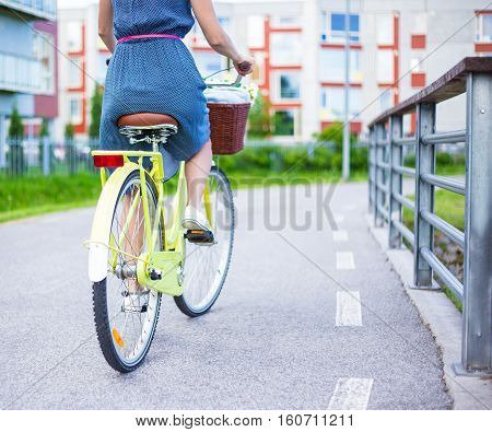 Back View Of Woman In Dress Riding Vintage Bike With Basket