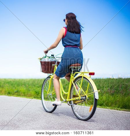 Back View Of Woman Riding Vintage Bicycle With Basket In Countryside
